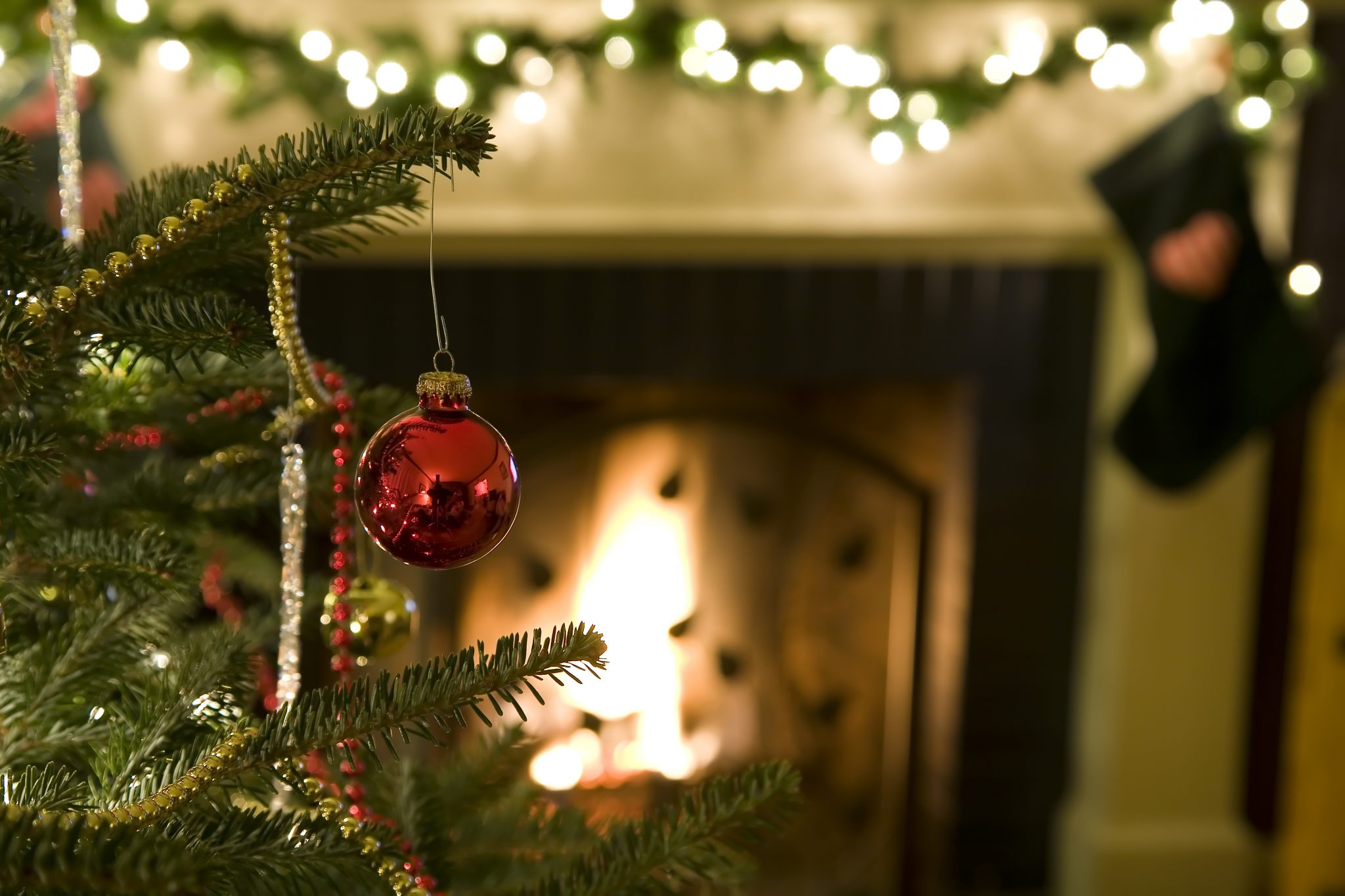 A close up of a decorated Christmas tree in front a fireplace with Christmas lights and a stocking.